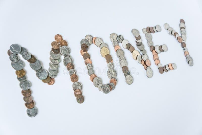 Moedas isoladas no fundo branco contínuo que soletra o dinheiro da palavra foto de stock