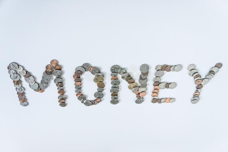 Moedas isoladas no fundo branco contínuo que soletra o dinheiro da palavra imagens de stock royalty free