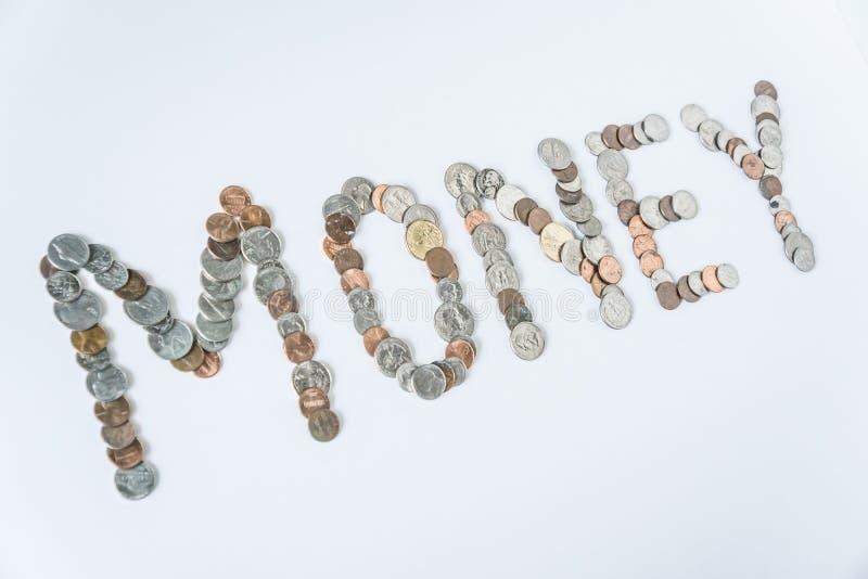 Moedas isoladas no fundo branco contínuo que soletra o dinheiro da palavra fotos de stock royalty free