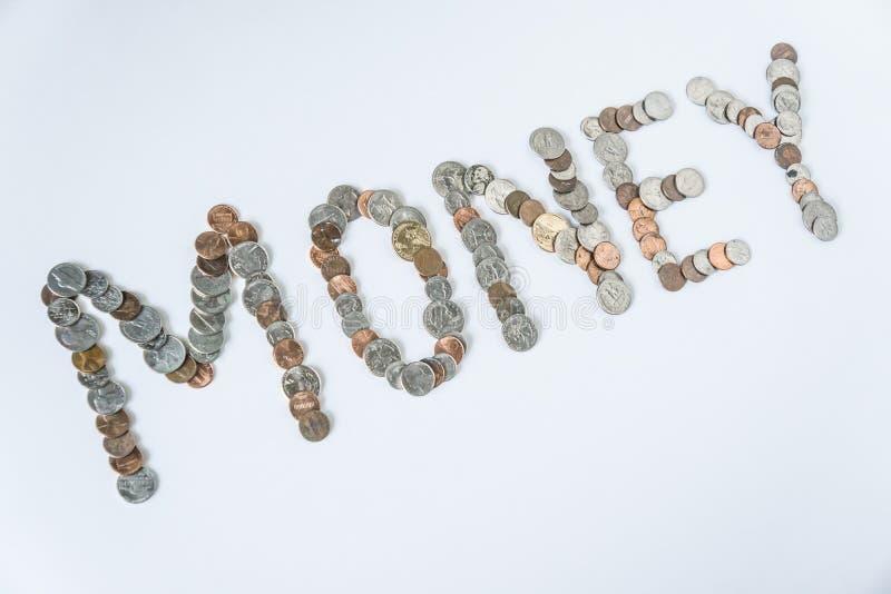 Moedas isoladas no fundo branco contínuo que soletra o dinheiro da palavra fotografia de stock royalty free