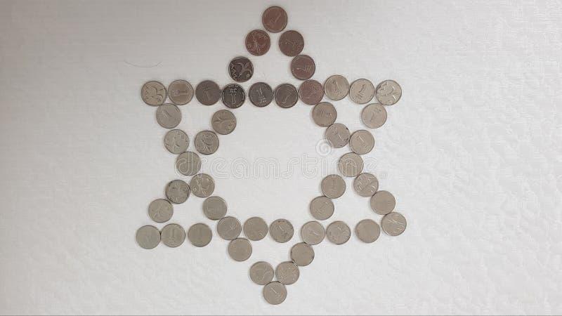 Moedas israelitas de um metal do shekel arranjadas no fundo branco em uma forma de seis pontos judaicos da estrela foto de stock royalty free