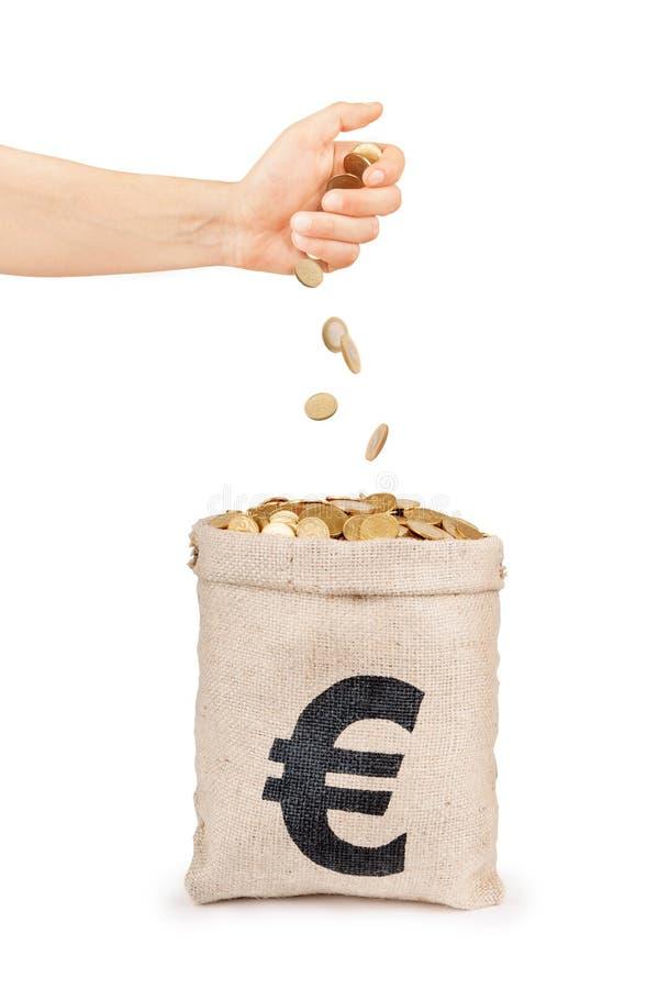 Moedas que caem da mão no saco com moedas imagens de stock royalty free