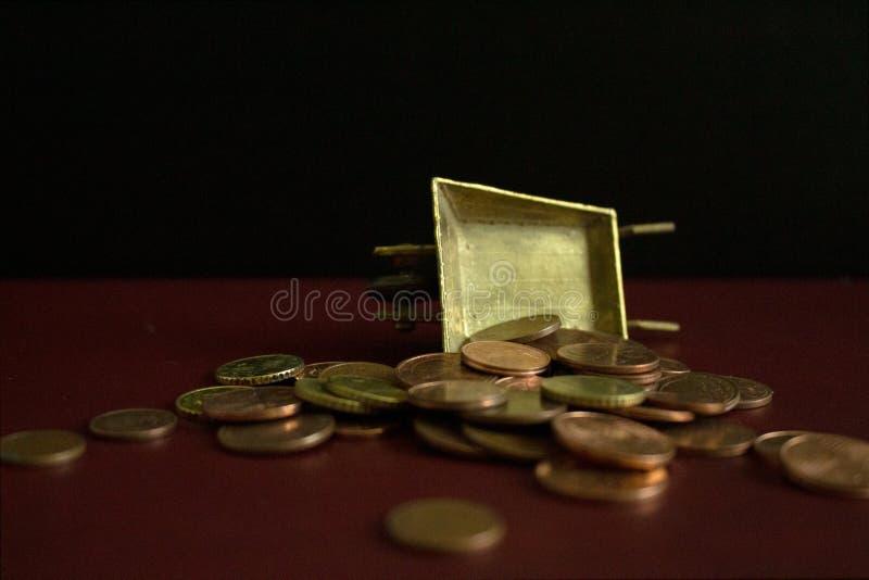 Moedas que caem de um carrinho de mão dourado do vintage imagem de stock