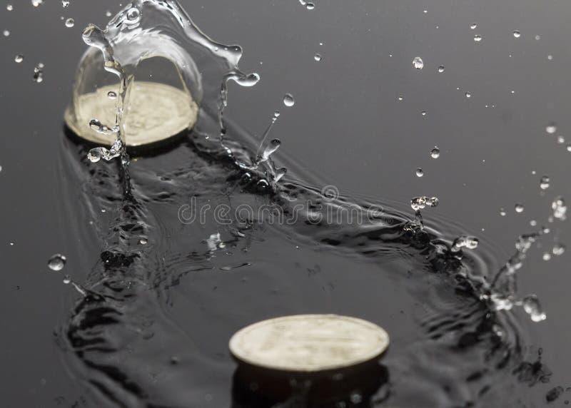 Moedas que saltam na água foto de stock