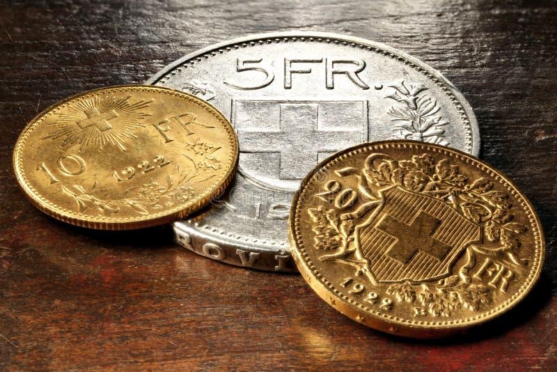 Moedas suíças da prata e de ouro imagem de stock royalty free