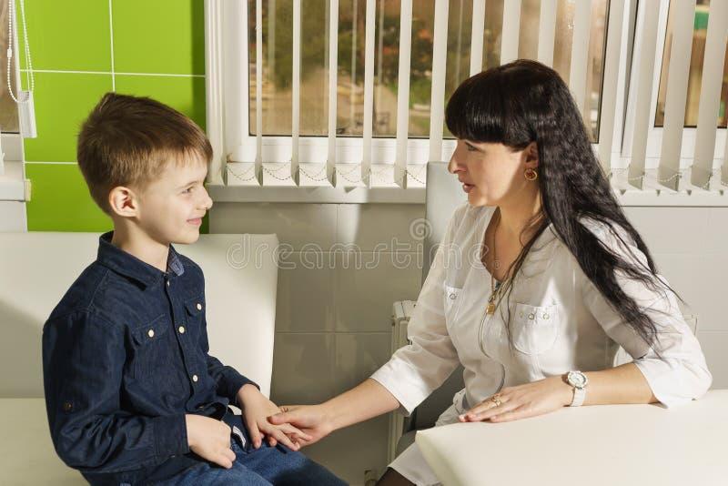 Moeder arts die met een jonge zoon in zijn bureau spreken De liefde en de zorg van een moeder royalty-vrije stock foto