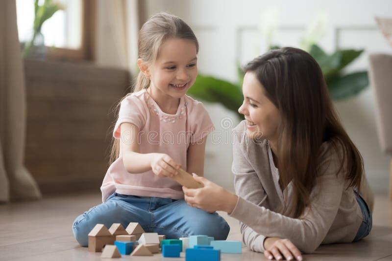 Moeder of babysitterspel met weinig jong geitje met stuk speelgoed blokken stock foto
