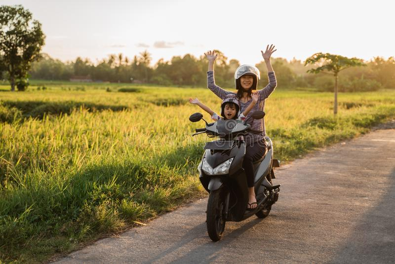 Moeder berijdende motorfiets met dochter stock afbeelding