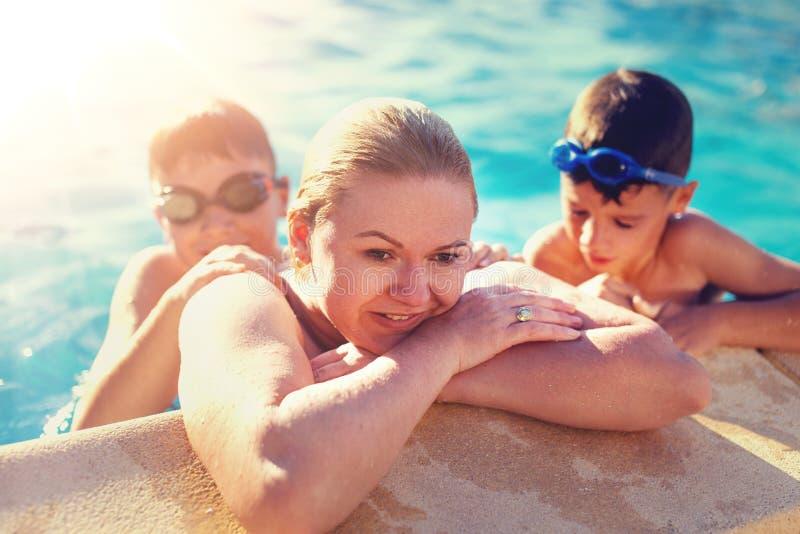 Moeder bij rand van zwembad met zonen stock afbeeldingen