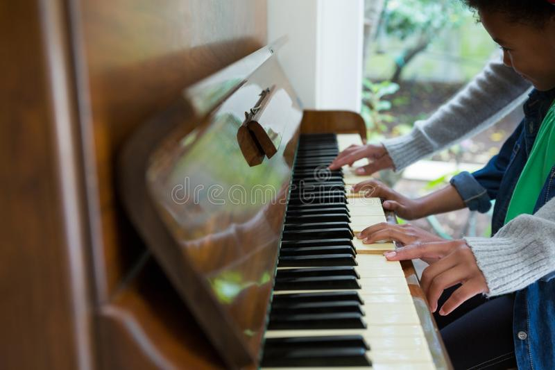 Moeder bijwonende dochter in het spelen piano stock foto