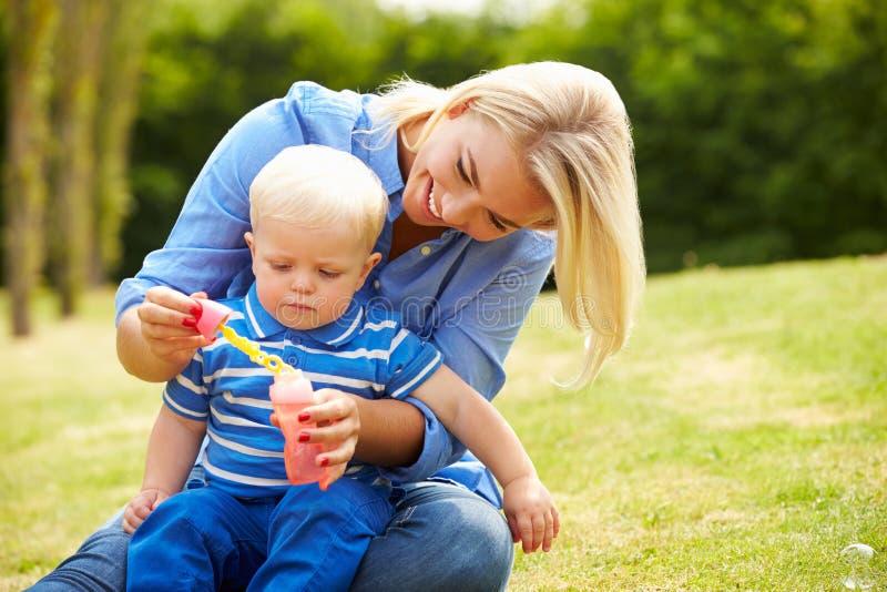 Moeder Blazende Bellen voor Jonge Jongen in Tuin stock foto