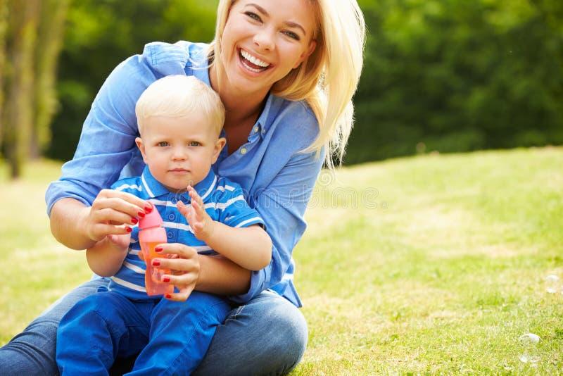 Moeder Blazende Bellen voor Jonge Jongen in Tuin stock afbeeldingen