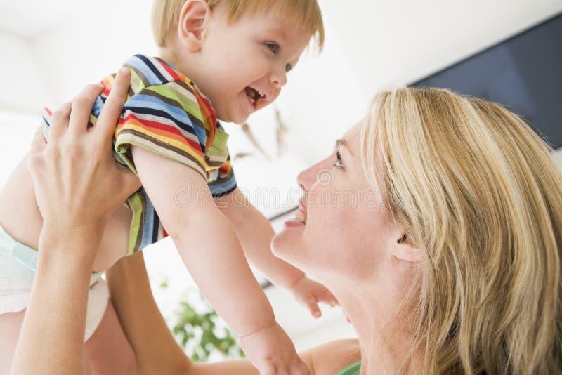 Moeder in de baby van de woonkamerholding stock afbeelding