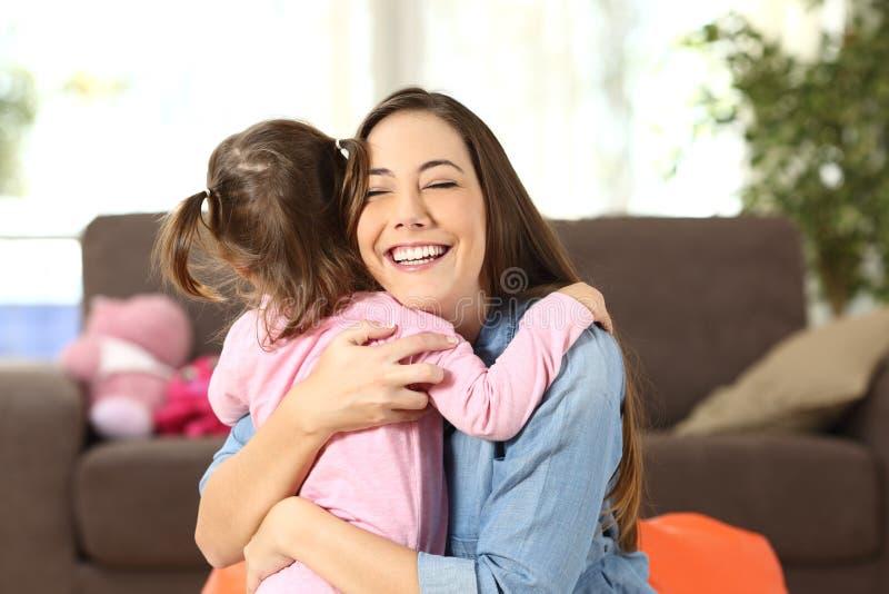 Moeder die aan haar babydochter omhelzen stock afbeelding