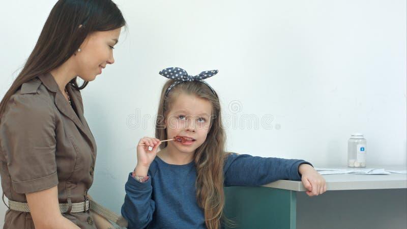 Moeder die aan haar meisje spreken die een lolly eten op artsen` s kantoor royalty-vrije stock afbeelding