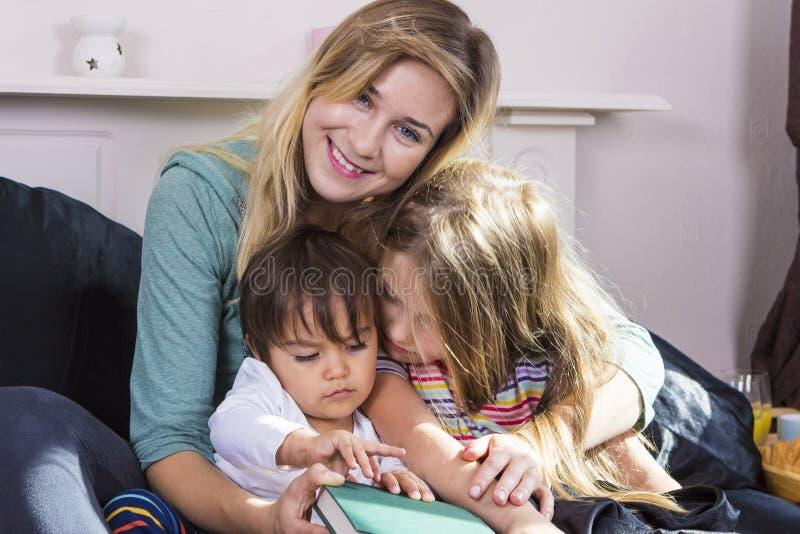 Moeder die aan jonge geitjes in bed lezen royalty-vrije stock foto's