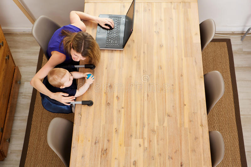 Moeder die aan laptop werken en met haar zoon spelen royalty-vrije stock afbeeldingen