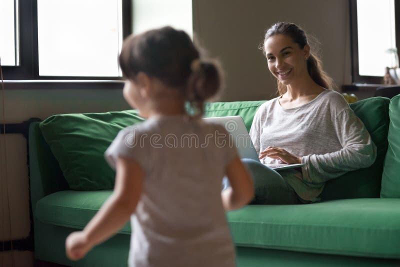 Moeder die aan laptop werken terwijl jong geitjemeisje die thuis spelen stock foto's