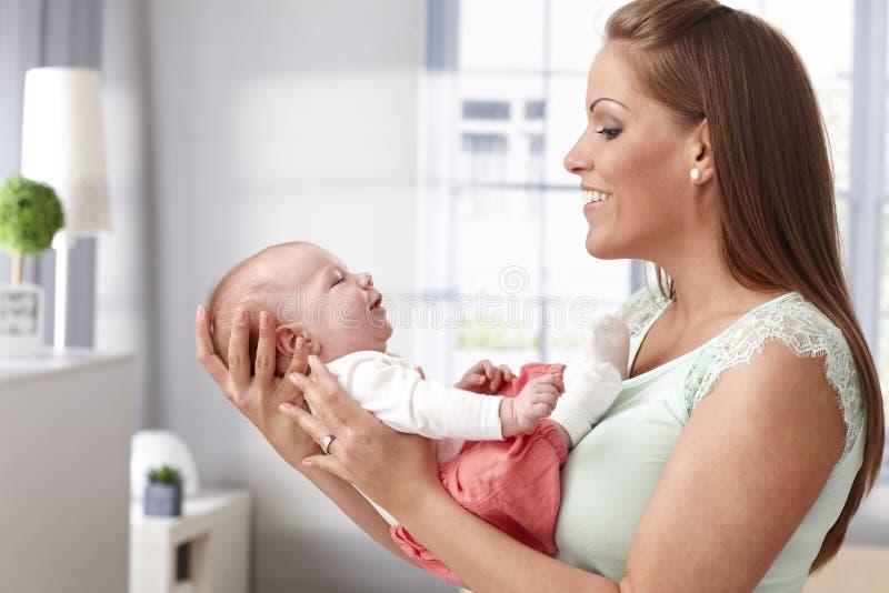 Moeder die aan pasgeboren baby glimlachen royalty-vrije stock afbeeldingen