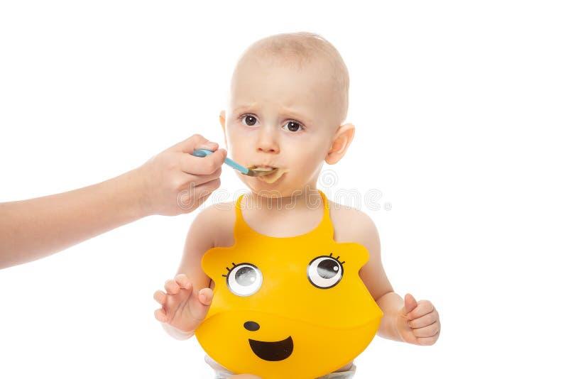 Moeder die Aanbiddelijke Babyjongen in gele slab voeden familie, voedsel, het eten en mensenconcept - gelukkige moeder met puree  stock foto's