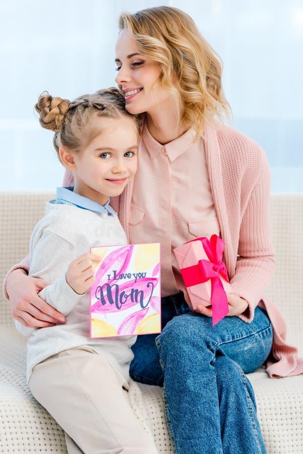 moeder die aanbiddelijke dochter koesteren en prentbriefkaar op gelukkig tonen royalty-vrije stock foto