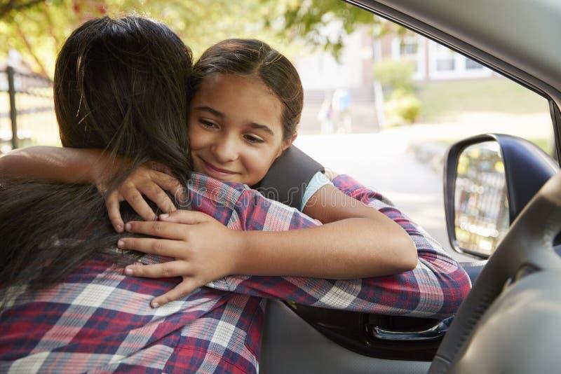 Moeder die in Auto Dochter in Front Of School Gates afzetten stock foto
