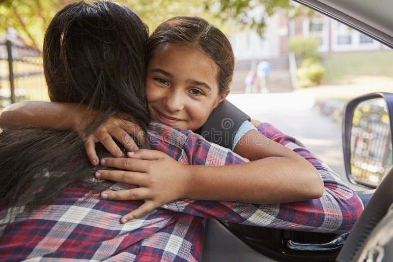 Moeder die in Auto Dochter in Front Of School Gates afzetten stock afbeelding