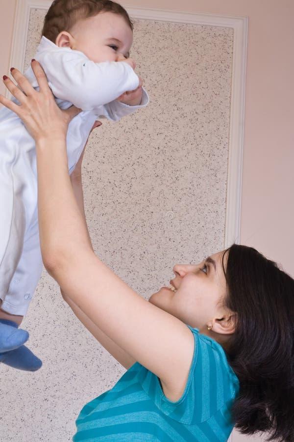 Moeder die baby in de lucht in de ruimte werpt stock foto's