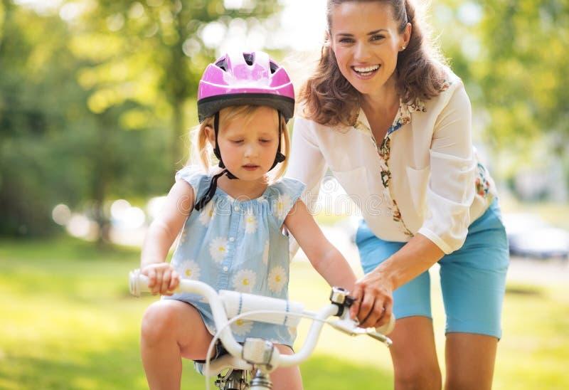 Moeder die babymeisje helpen die op fiets berijden stock foto