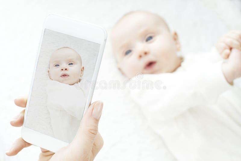Moeder die Beeld van Babymeisje nemen op Mobiele Telefoon stock afbeeldingen