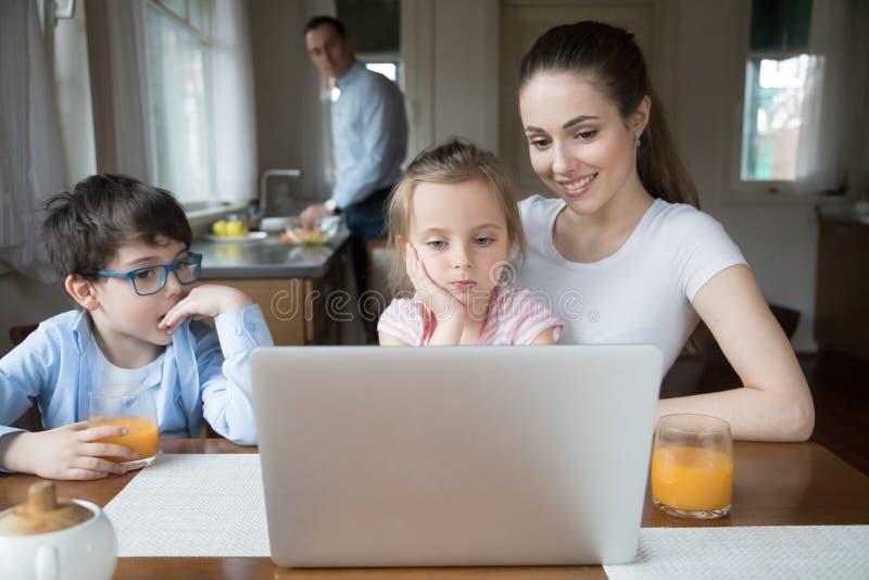 Moeder die beeldverhaal op computer voor kinderen tonen terwijl vader het koken stock fotografie