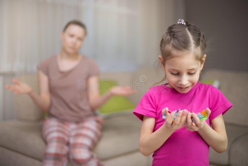 Moeder die dat haar dochter veel suikergoed eet frustreren stock afbeeldingen