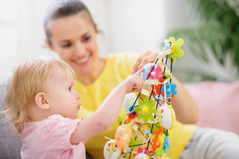 Moeder die de baby gemaakte decoratie van Pasen helpt royalty-vrije stock afbeeldingen
