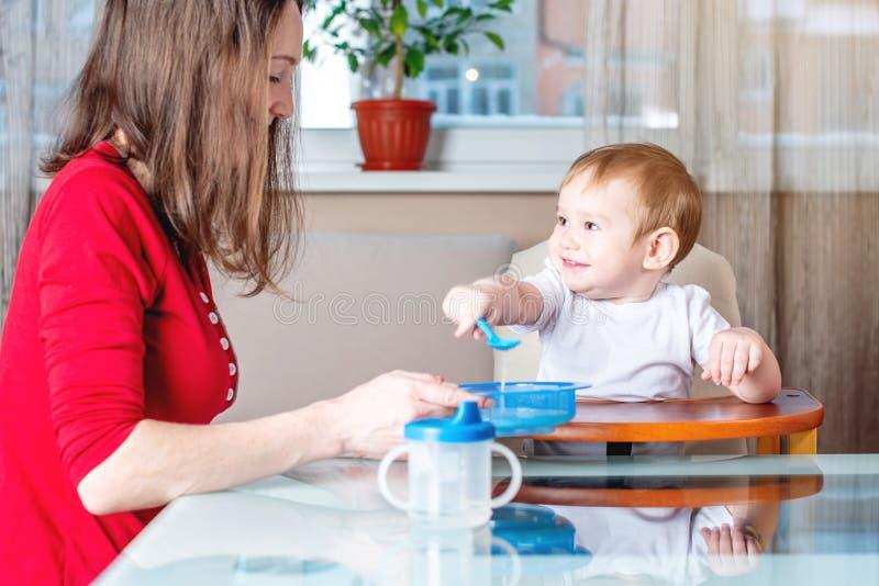 Moeder die de hand van de babyholding met een lepel van voedsel voeden Gezonde babyvoeding De emoties van een kind terwijl het et stock fotografie