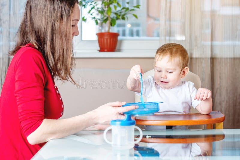 Moeder die de hand van de babyholding met een lepel van voedsel voeden Gezonde babyvoeding De emoties van een kind terwijl het et stock foto
