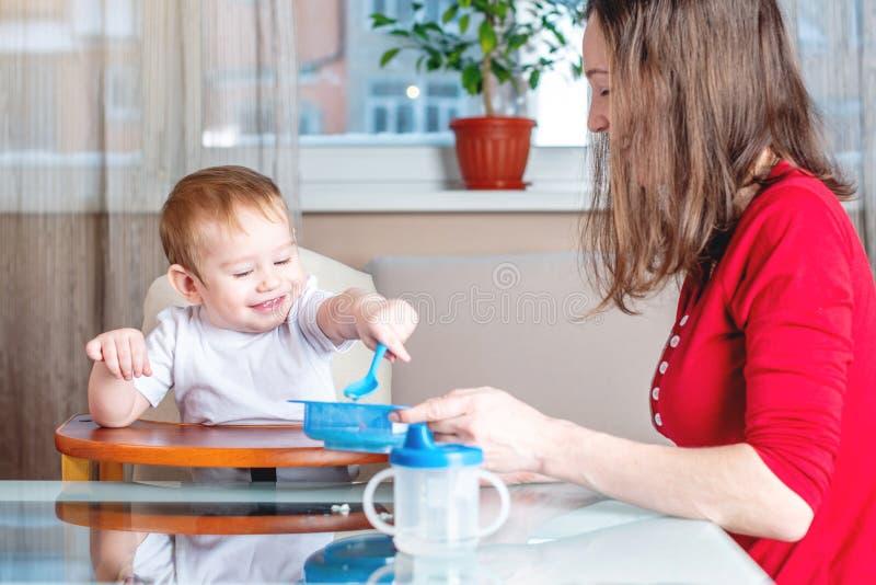 Moeder die de hand van de babyholding met een lepel van voedsel voeden Gezonde babyvoeding De emoties van een kind terwijl het et royalty-vrije stock fotografie