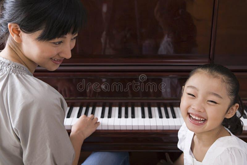 Moeder die de piano voor haar dochter spelen stock foto