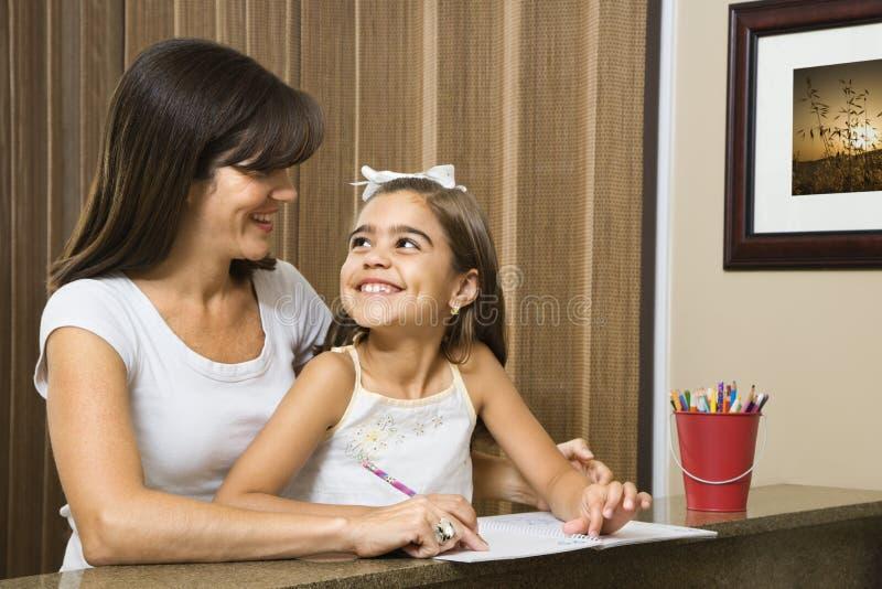 Moeder die dochter helpt. royalty-vrije stock afbeeldingen