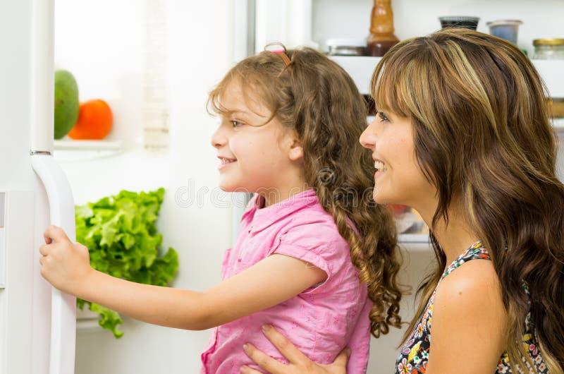 Moeder die dochter steunen die in de moderne deur van de keuken openingskoelkast binnen gelukkig kijken royalty-vrije stock foto