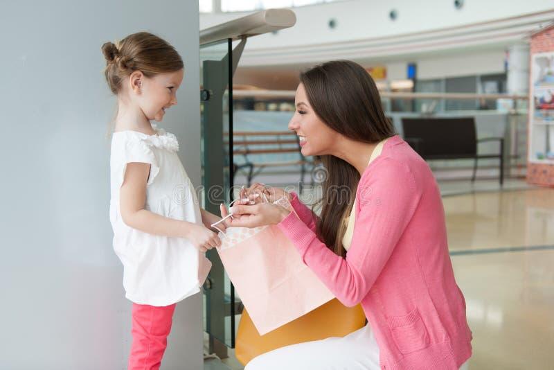 Moeder die dochterdocument het winkelen zak geven stock fotografie