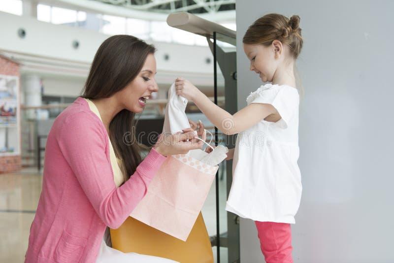 Moeder die dochtergift van document het winkelen zak geven royalty-vrije stock afbeeldingen