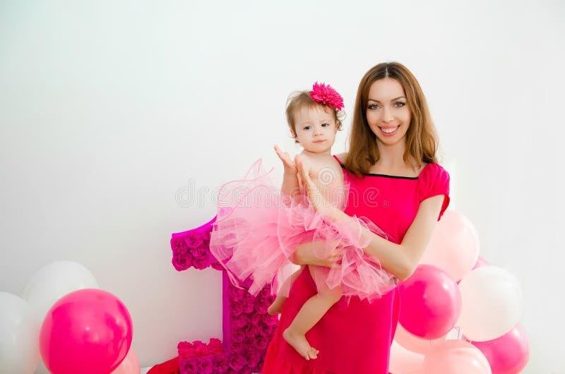 Moeder die een baby in haar wapens houdt Meisje in een roze rok stock foto's