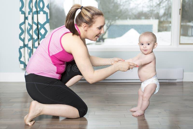 Moeder die een baby houden onder zijn wapens in woonkamer royalty-vrije stock fotografie