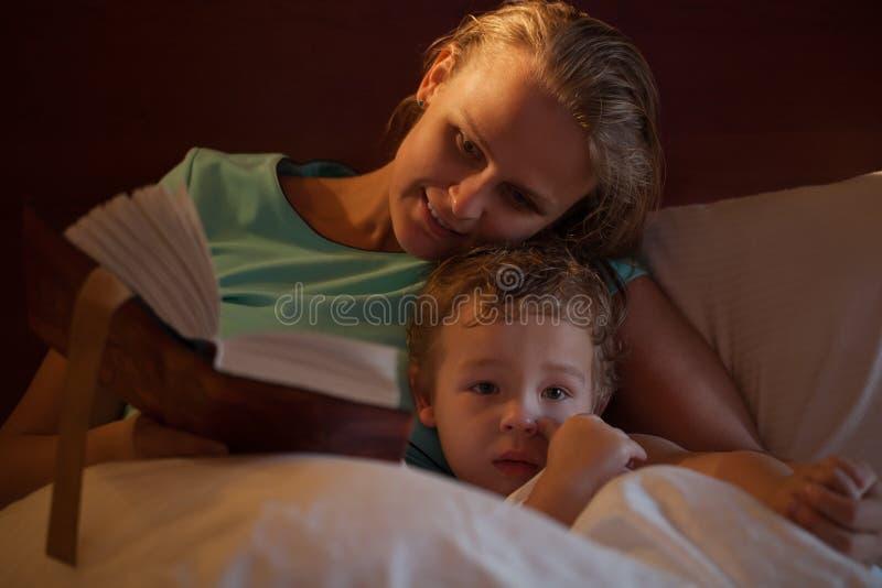 Moeder die een bedtijdverhaal lezen aan haar weinig zoon stock fotografie