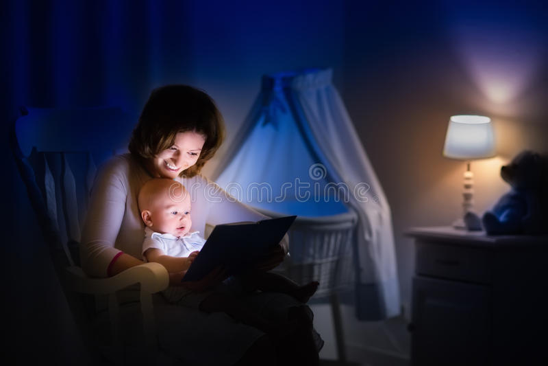 Moeder die een boek lezen aan weinig baby royalty-vrije stock afbeeldingen