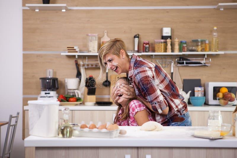 Moeder die een goede tijd met haar tienerdochter hebben terwijl het koken royalty-vrije stock foto's