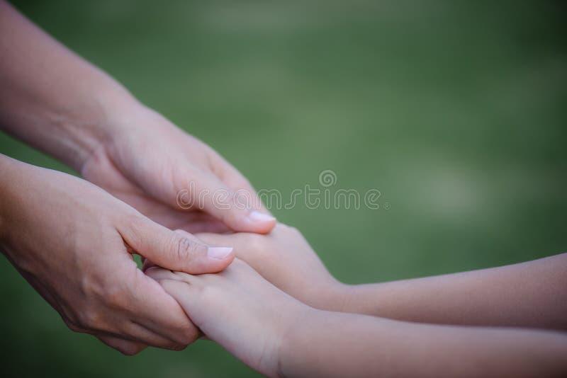 Moeder die een hand van zijn zoon met groene glasachtergrond houden stock foto's