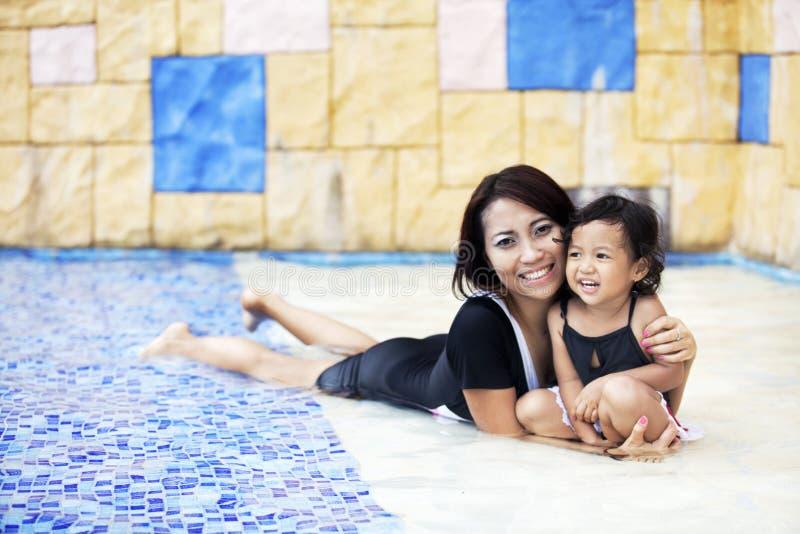 Moeder die een kwaliteitstijd heeft bij zwembad royalty-vrije stock afbeelding