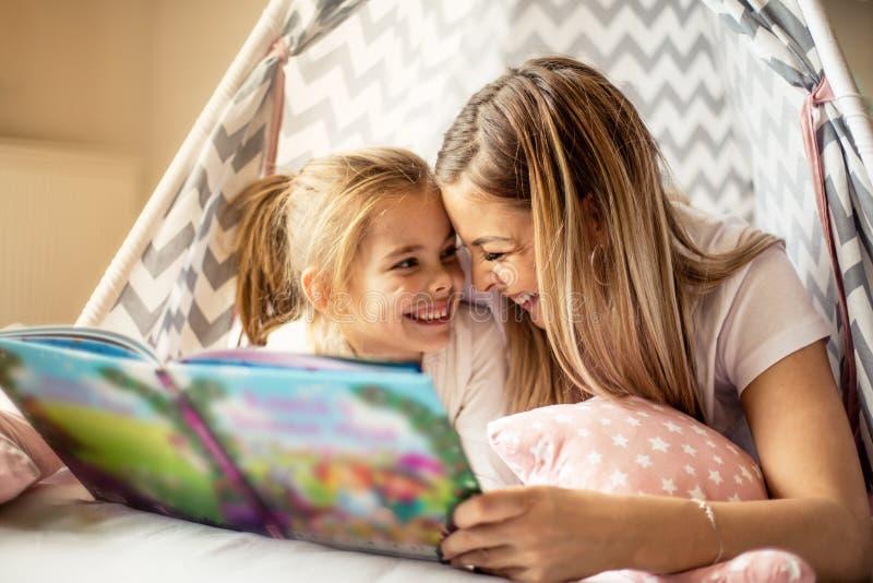 Moeder die een verhaal lezen aan haar dochter stock foto