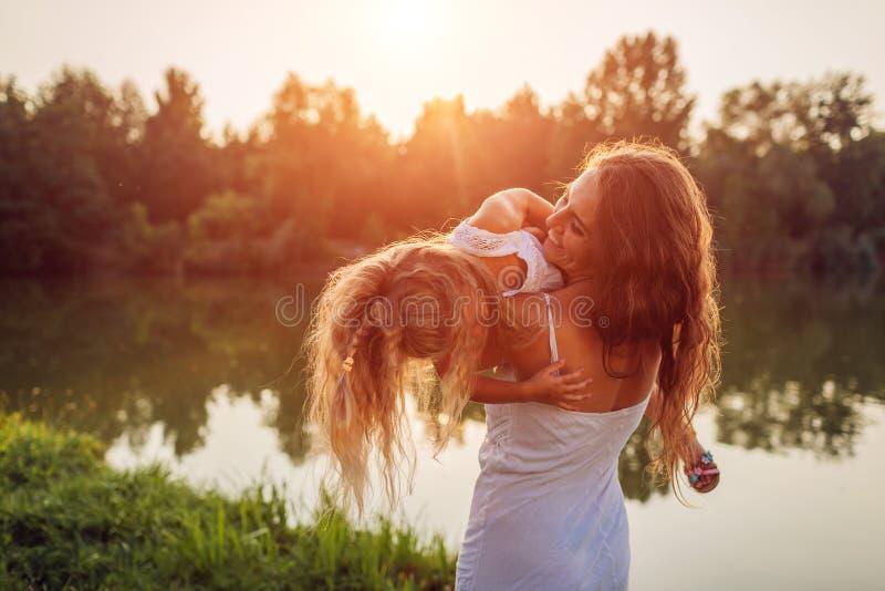 Moeder die en pret met dochter spelen hebben door de zomerrivier bij zonsondergang Vrouwenholding jong geitje en het lachen Famil stock foto's